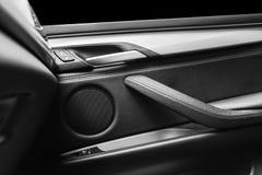 Tirador de puerta con los botones del control del elevalunas eléctrico de un vehículo de pasajeros de lujo Interior de cuero negr Imagen de archivo libre de regalías