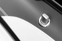 Tirador de puerta con los botones del control de la cerradura de un vehículo de pasajeros de lujo Interior de cuero negro del coc Foto de archivo