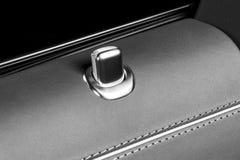 Tirador de puerta con los botones del control de la cerradura de un vehículo de pasajeros de lujo Interior de cuero rojo del coch Imágenes de archivo libres de regalías