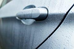 Tirador de puerta mojado de un sedán de lujo Imágenes de archivo libres de regalías