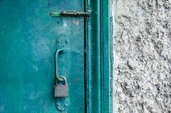 Tirador de puerta texturizado con la cerradura, en la puerta verde vieja Foto de archivo