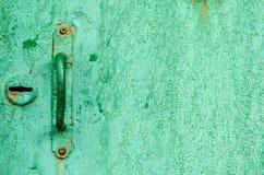 Tirador de puerta texturizado en una puerta verde vieja Fotografía de archivo libre de regalías