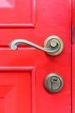 Tirador de puerta viejo del vintage en puerta roja Fotos de archivo libres de regalías