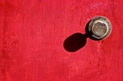 Tirador de puerta viejo en puerta roja Imagen de archivo libre de regalías