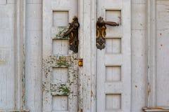 Tiradores de puerta asimétricos en una puerta de madera texturizada, rasguñada blanca Marrón y gris oscuros, manetas palanca de l foto de archivo