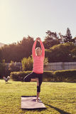 Étirage supérieur dans une pose de équilibrage de yoga dehors Photos stock