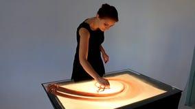 Tiragem com areia Areia do desenho em uma tela O artista Hands da areia tira animation vídeos de arquivo