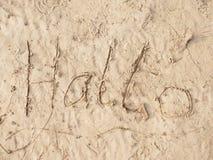 Tiragem das crianças da palavra olá! na areia na praia da baía Letras escritas na areia Fotos de Stock