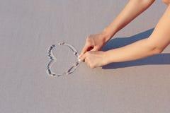 Tiragem no símbolo do coração da areia da praia fotos de stock royalty free