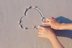 Tiragem no símbolo do coração da areia da praia Imagem de Stock Royalty Free