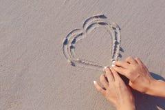 Tiragem no símbolo do coração da areia da praia Imagem de Stock