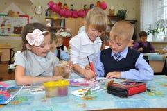 Tiraggio dei bambini ad una lezione a scuola primaria fotografia stock