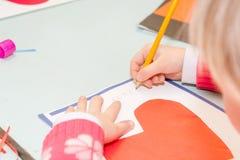Tiraggio del bambino una cartolina I bambini sono impegnati in cucito La ragazza firma una cartolina il 14 febbraio fotografie stock libere da diritti