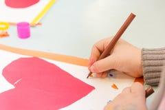 Tiraggio del bambino una cartolina I bambini sono impegnati in cucito La ragazza firma una cartolina il 14 febbraio immagine stock libera da diritti