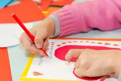 Tiraggio del bambino una cartolina I bambini sono impegnati in cucito La ragazza firma una cartolina il 14 febbraio fotografia stock