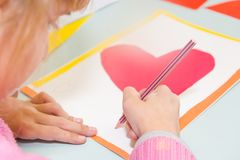 Tiraggio del bambino una cartolina I bambini sono impegnati in cucito La ragazza firma una cartolina il 14 febbraio immagini stock libere da diritti