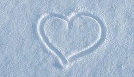 Tiraggio di cuore sulla neve bianca fotografie stock