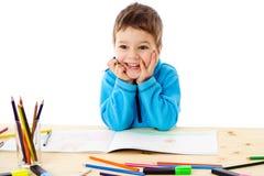 Tiraggio sorridente del ragazzino con i pastelli immagine stock