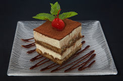 Tiramisu cake. With mint and cherry on plate Royalty Free Stock Image