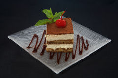 Tiramisu cake. With cherry and mind on plate Royalty Free Stock Image