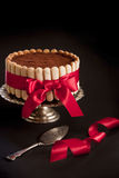 Tiramisu cake. Tiramisu charlotte cake with red ribbon on a silver stand with silver cake server on a black background stock photography