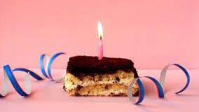 Tiramisu cake with burning blue candle on pink background and confetti