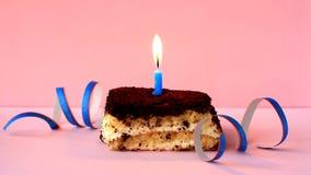 Tiramisu cake with burning blue candle on pink background and confetti. Time lapse video
