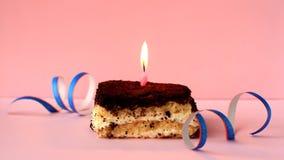 Tiramisu cake with burning pink candle on pink background and confetti. Time lapse video