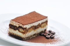 Tiramisu cake with cocoa powder and coffee beans on white plate, photography for patisserie, sponge cake Royalty Free Stock Photo