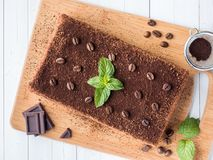 Tiramisu cake with coffee beans and fresh mint chocolate on the Board in white background Close up Stock Images