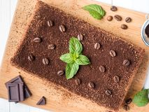 Tiramisu cake with coffee beans and fresh mint chocolate on the Board in white background Close up Royalty Free Stock Images