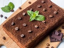 Tiramisu cake with coffee beans and fresh mint chocolate on the Board in white background Close up Royalty Free Stock Image