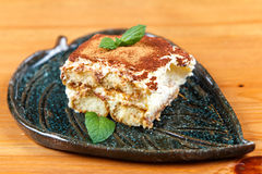 Tiramisu cake on decorated plate. On the wooden board Stock Image