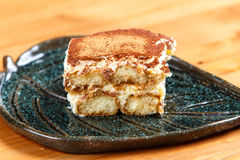 Tiramisu cake on decorated plate. On the wooden board Stock Photography