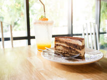 Tiramisu cake and Glass of orange soda on wooden table Stock Photography