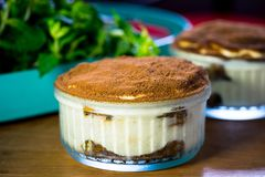 Tiramisu cake on glass. Tiramisu is a popular coffee-flavoured Italian dessert. It is made of ladyfingers dipped in coffee, layered with a whipped mixture of Stock Image