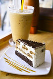 Tiramisu cake. Layer chocolate cake on white plate with ice coffee background Stock Images