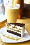 Tiramisu cake. Layer chocolate cake on white plate with ice coffee background Stock Photo