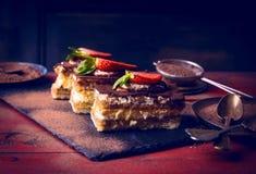 Tiramisu com as morangos no fundo de madeira escuro Imagem de Stock