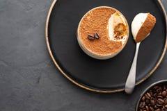 Tiramisu de dessert, chocolat, cacao et grains de café italiens délicieux sur un fond noir Vue supérieure avec l'espace de copie photographie stock