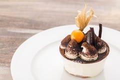 Tiramisu deseru tort z zmielonym czereśniowym zbliżeniem na bielu talerzu i drewnianym stole Obraz Royalty Free
