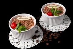 Tiramisu dessert on black background. Tiramisu dessert, with chocolate, decorated by cherry and mint on black background Royalty Free Stock Images