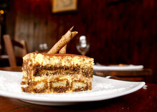 Tiramisu Dessert Cake. Plate of the Italian traditional dessert Tiramisu. Layers of sponge with cream dusted with chocolate and with a rolled wafer. Restaurant stock photo