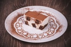 Tiramisu dessert slice on white plate Stock Images