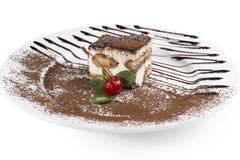 Tiramisu. Dessert Tiramisu sprinkled with chocolate chips, decorated with mint and cherries Royalty Free Stock Photography