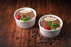 Tiramisu dessert on wooden background. Tiramisu dessert, with chocolate, decorated by cherry and mint on wooden background Stock Images