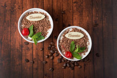 Tiramisu dessert on wooden background top view. Tiramisu dessert on wooden background, with chocolate, decorated by cherry and mint, top view Royalty Free Stock Photos