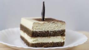 Tiramisu doce saboroso de giro do bolo na placa branca vídeos de arquivo