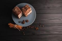 Tiramisu doux de dessert dans une coupe d'un plat gris sur un fond en bois noir avec des épices : bâtons de cannelle et badan Photo stock