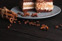 Tiramisu doux de dessert dans une coupe d'un plat gris sur un fond en bois noir avec des épices : bâtons de cannelle et badan Photographie stock